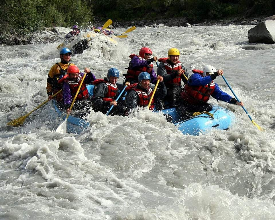 A group of people in a raft splashing through whitewater rapids.