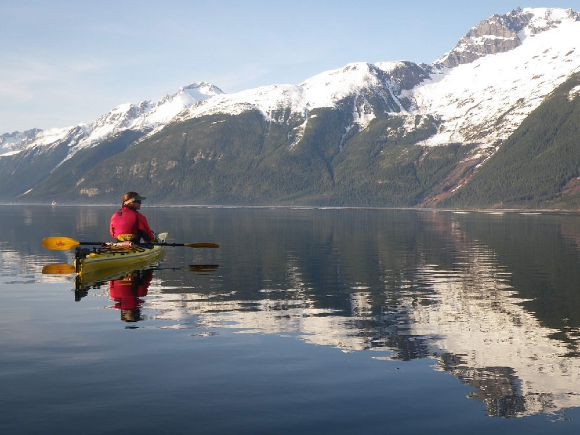 A person in a kayak on the water with snow capped mountains in the background