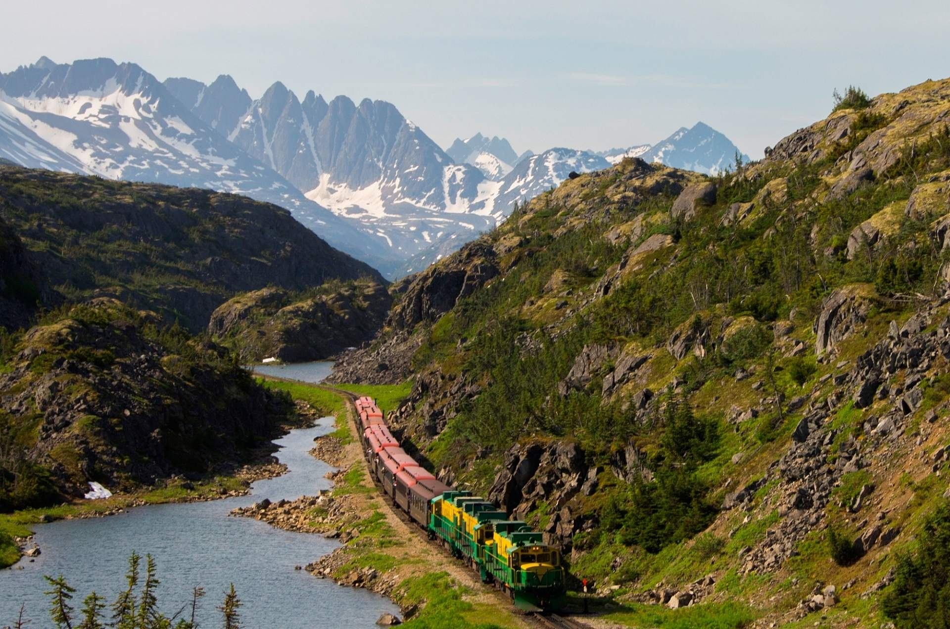 The train moving along the White Pass & Yukon Route surrounded by Alaska mountains and steams