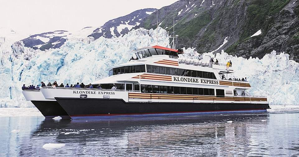 A day cruise ship on the water in front of a glacier.