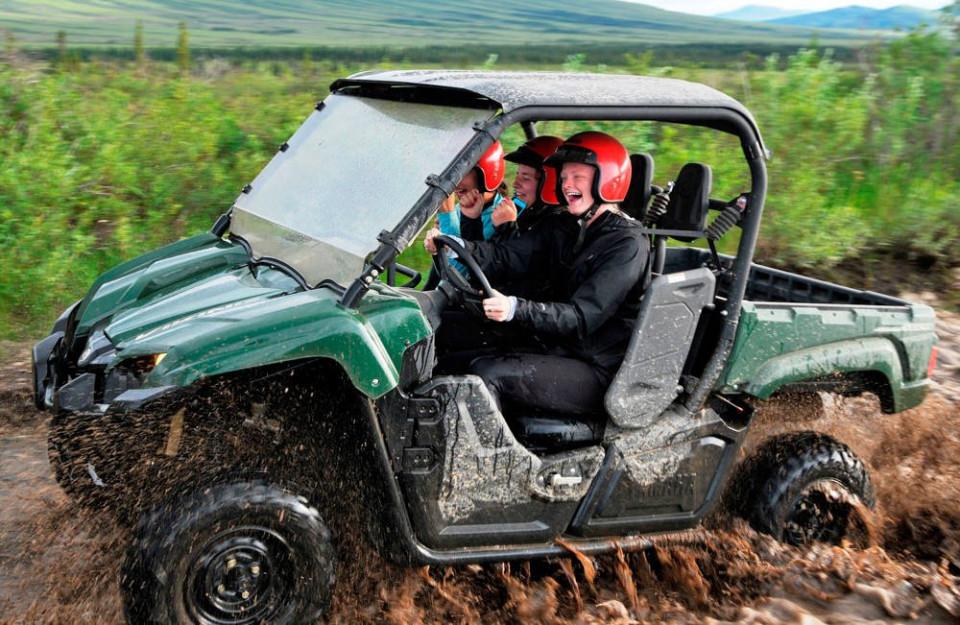 Three people smiling as they splash through the mud on an ATV