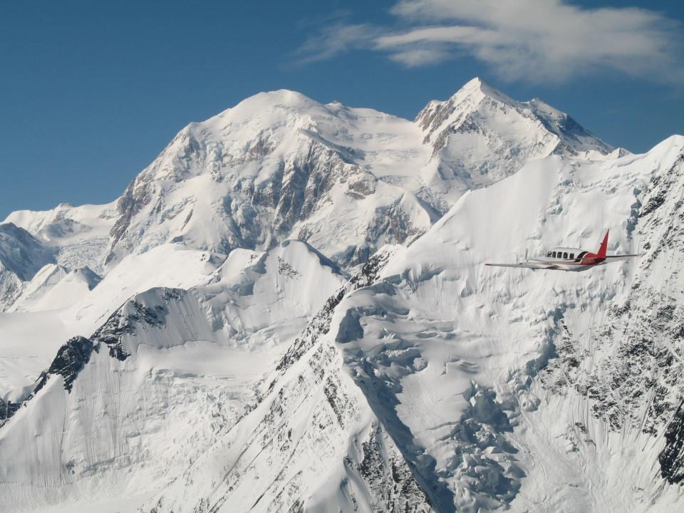 A flightseeing plane flies past snow capped Mt. Denali