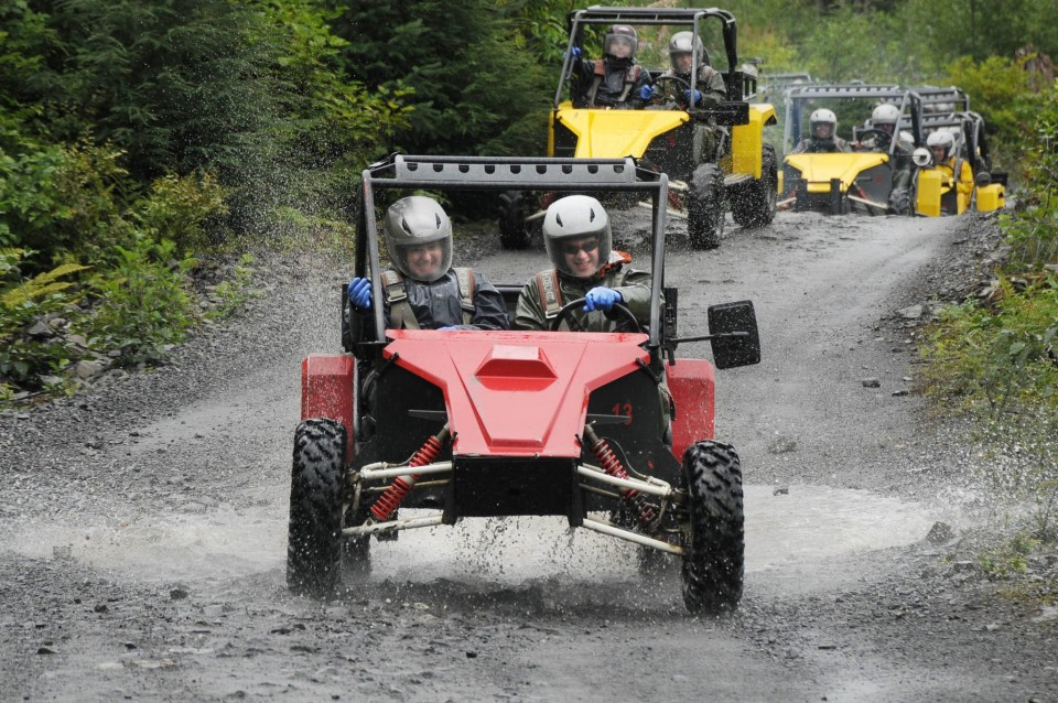Guests splash through the mud on ATVs with Alaska Kart Expedition