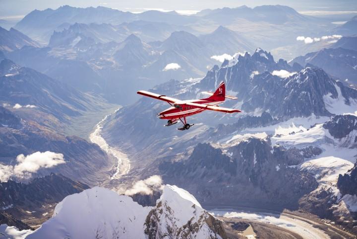 A small, red plane soars above a mountainous Alaskan landscape