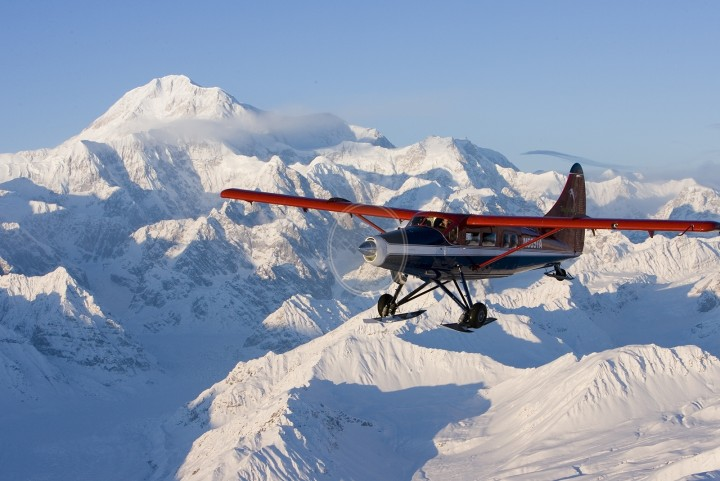 A small plane flies next to snow covered Mt. Denali.