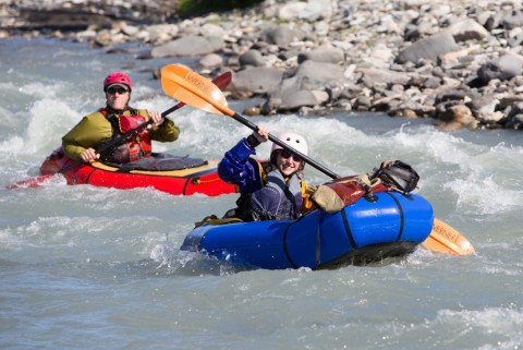 Two people in rafts paddle down a river