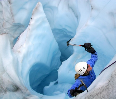 A person ice climbing on a glacier
