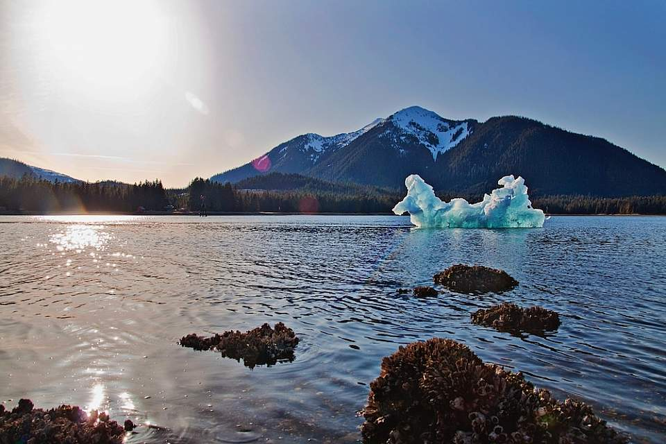 A giant iceberg that's broken off of LeConte Glacier floats in the water on a sunny day.