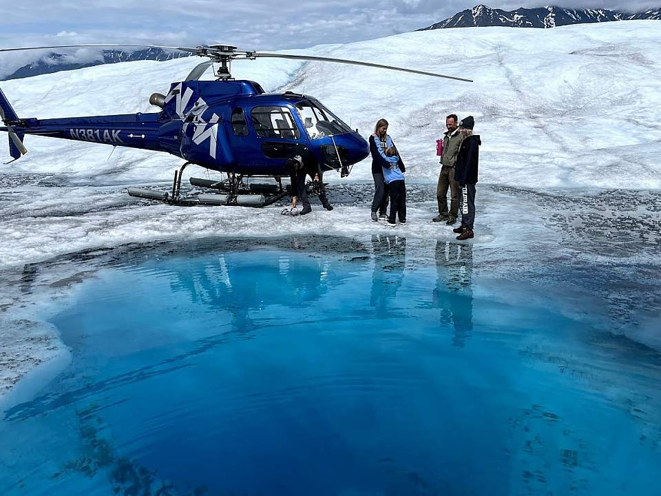 Helicopter lands near a bright blue glacier pool
