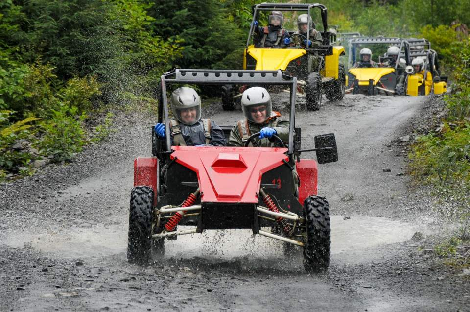 People in Tomcars race down a muddy forest trail.