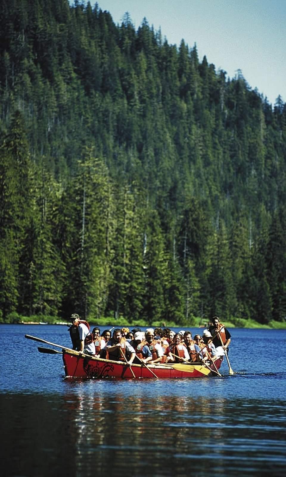 Paddle across a serene alpine lake in a traditional Alaska Native-style canoe