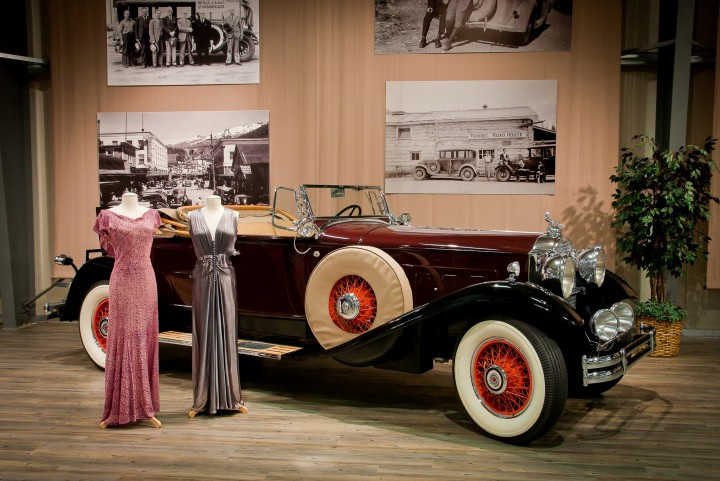 Two vintages dresses stand on display in front of a black and red vintage car with old photos displayed on the wall behind it