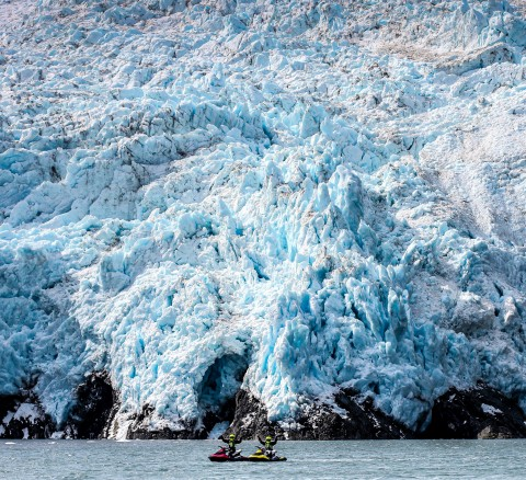Two jet skiers in dry suits and helmets pose on the water in front of a glacier.