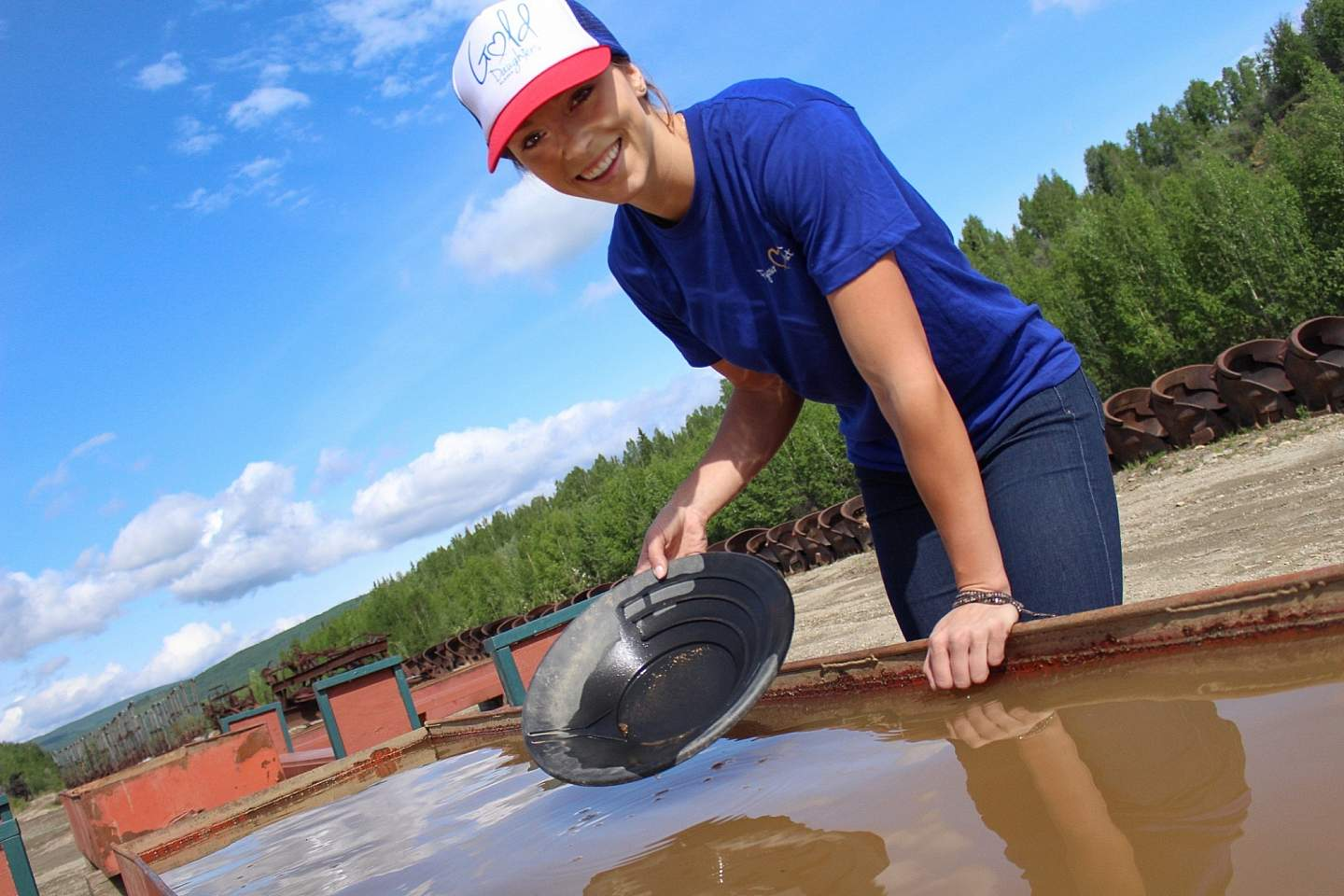 A smiling woman pans for gold outside.