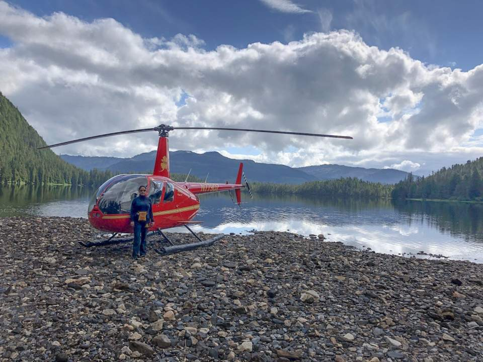 Pilot stands by their red helicopter that is landed on a rocky beach with mountains in the background.