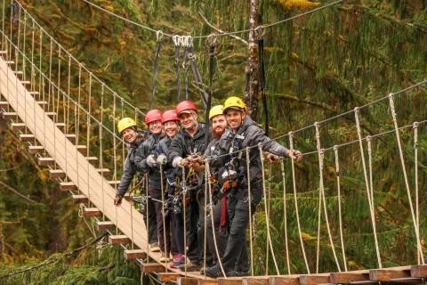 People in ziplining gear walking across a suspension bridge.