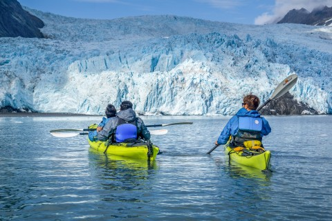 People kayaking on icy blue waters next to a glacier.