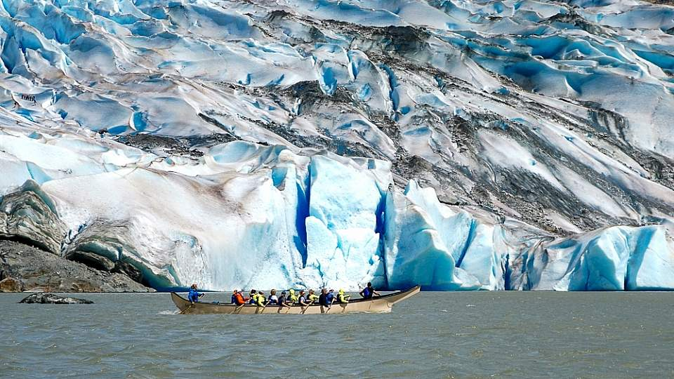 People row a canoe through the water towards a glacier.