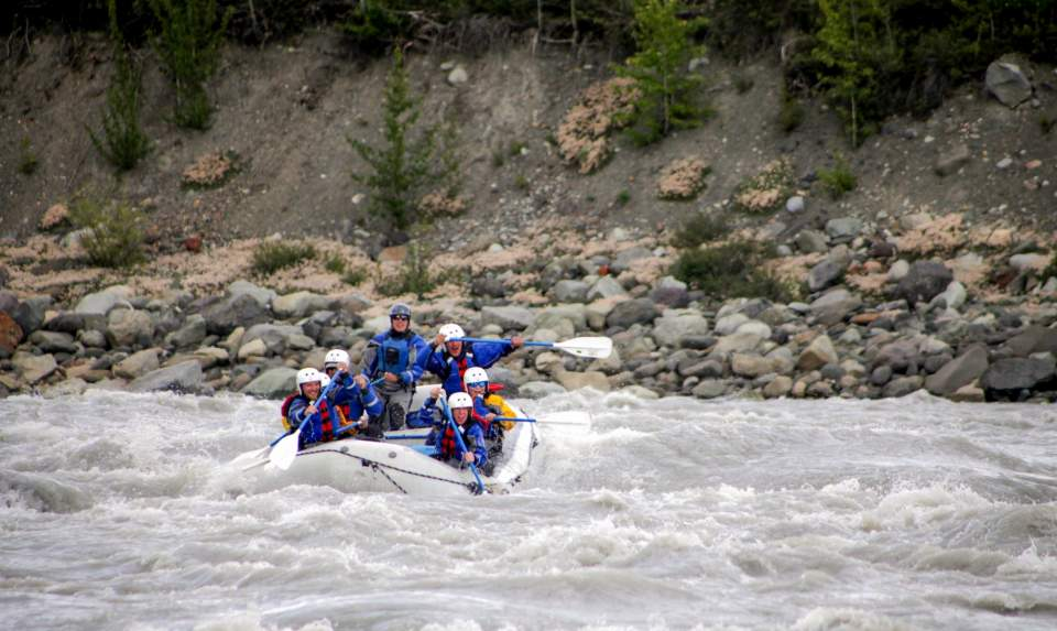 People rafting down a river on an inflatable raft.