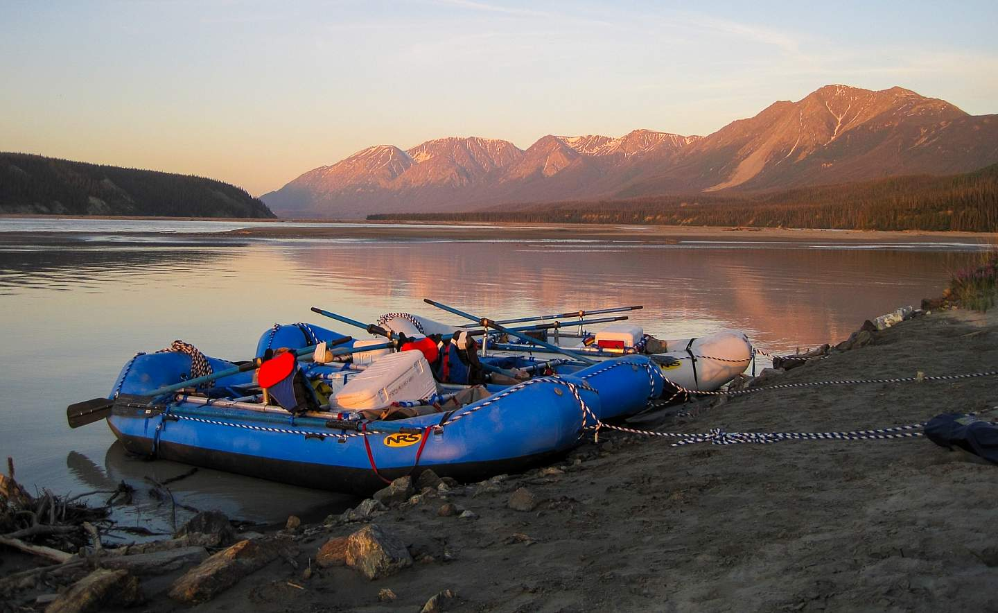 Inflatable rafts filled with camping gear docked on the beach of an Alaskan river.