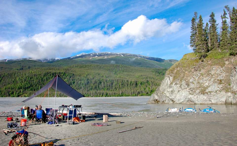 A campsite set up on the beach of an Alaskan river on a summer day.