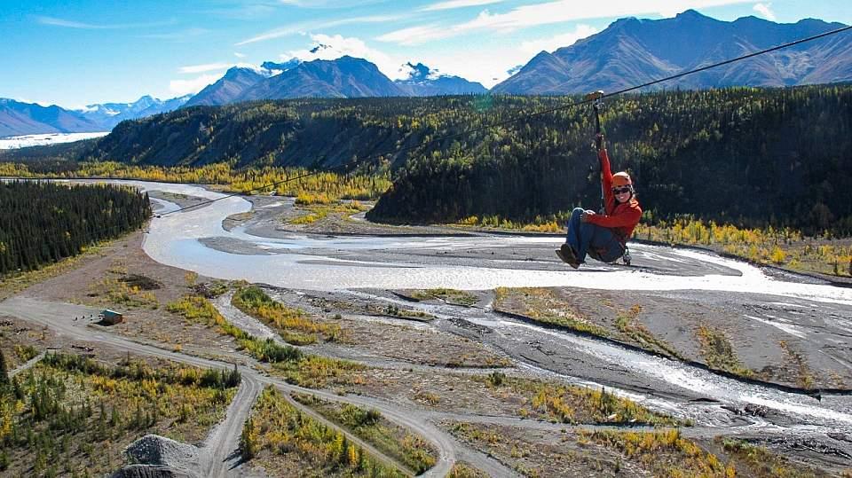 A person ziplining over an Alaskan valley.