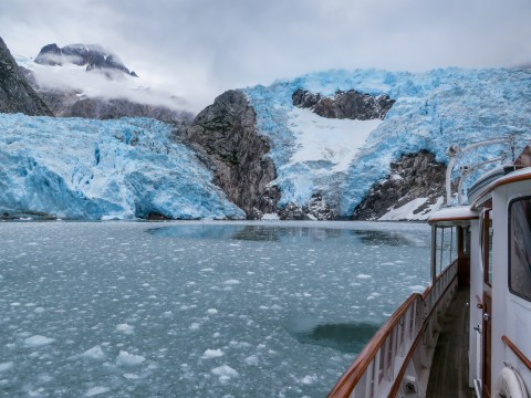 Look out from a boat at a glacier.