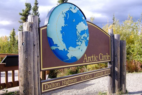 """A large wooden sign that says """"Arctic Circle""""."""