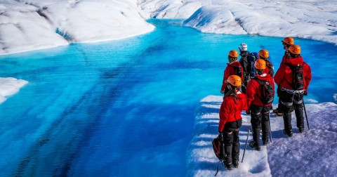 Hikers gaze at rich blue color of glacial pool