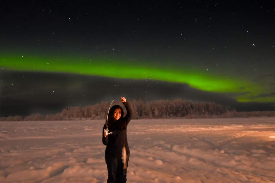 Vibrant green Northern Lights shine above someone who holds up a fish they caught while ice fishing.