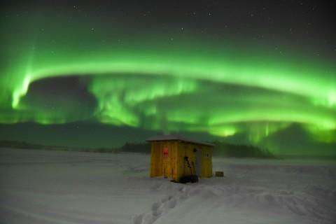 Vibrant green Northern Lights dance above an ice fishing hut.
