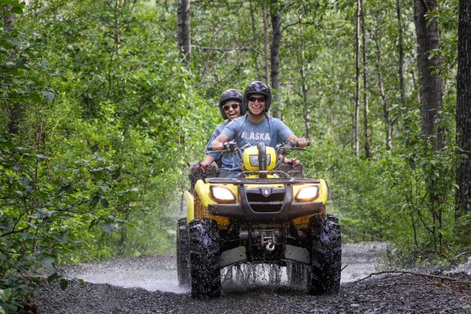 Two people ride an ATV down an Alaska forest trail.