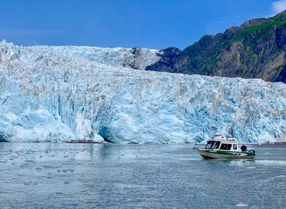 A small sightseeing boat cruises past a glacier.