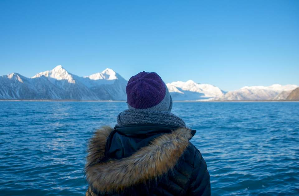 A person in winter clothing gazes at the blue waters of Resurrection Bay with snow covered mountains in the background.