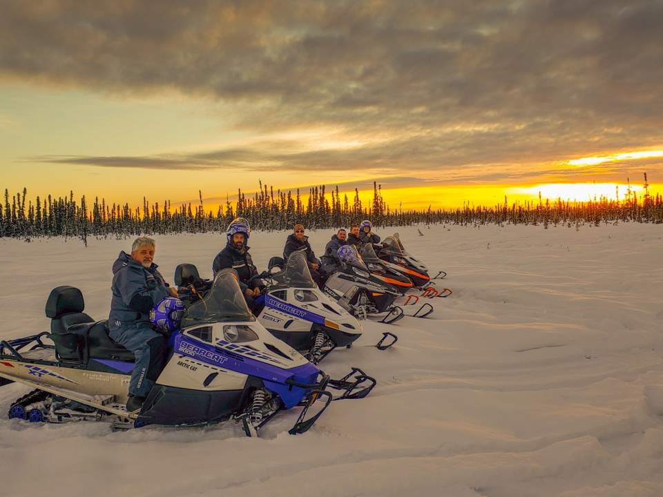 A group of people in a row on their snowmobile with a golden sunset in the background.