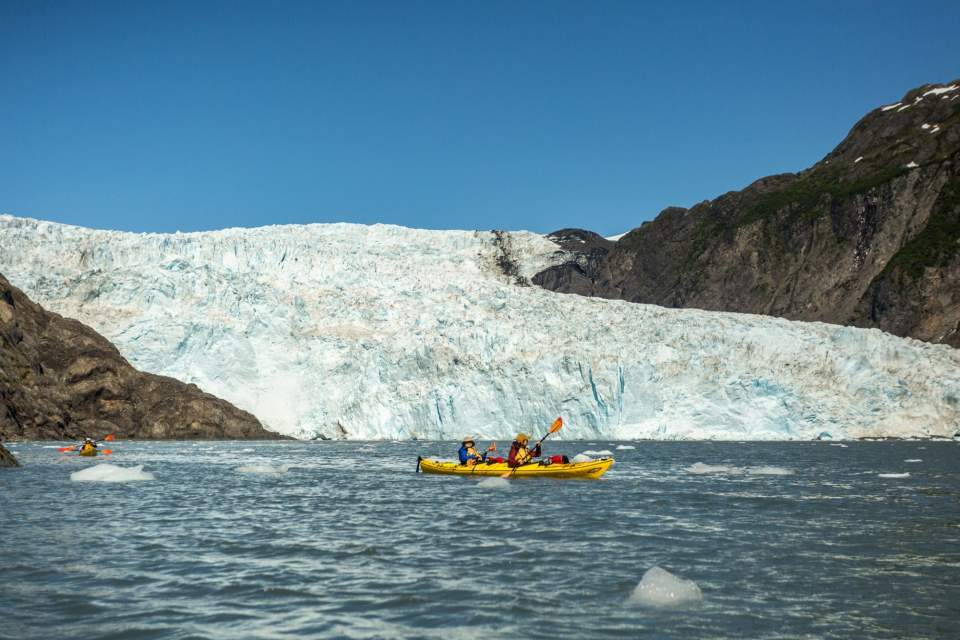 Two kayakers in front of a large, tidewater glacier