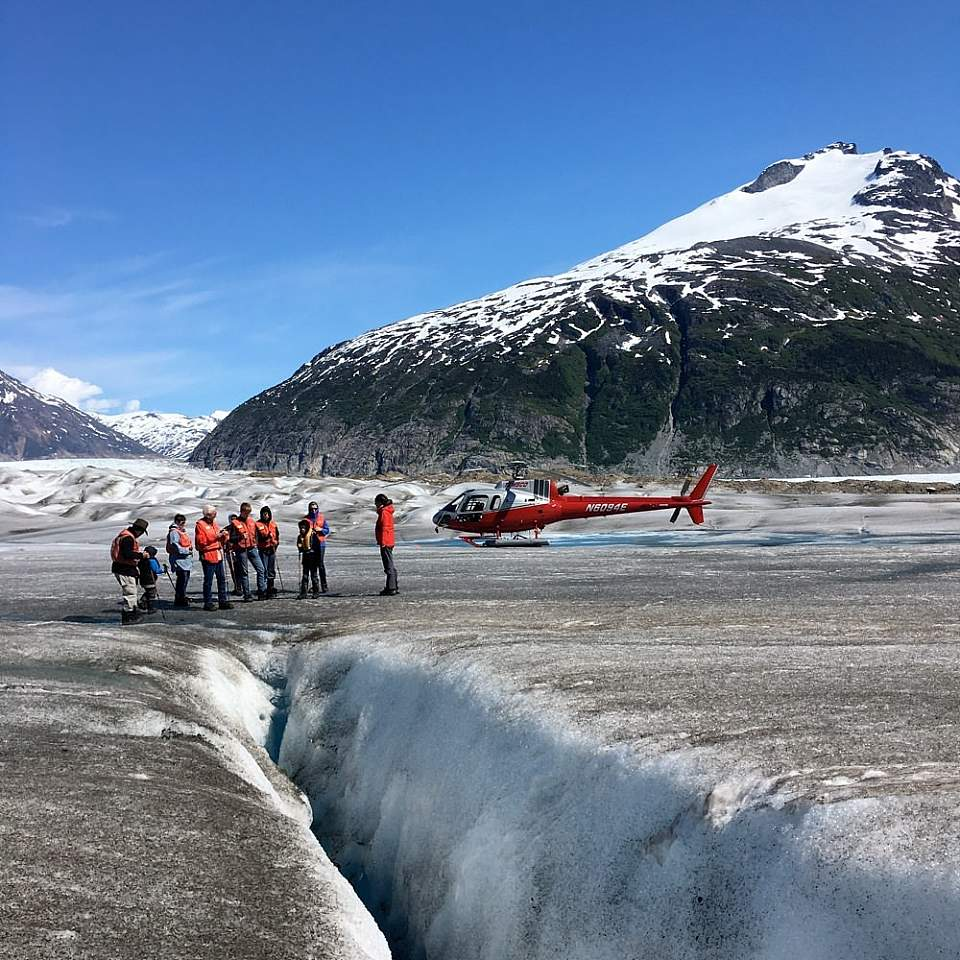 People walk on a glacier after landing by helicopter