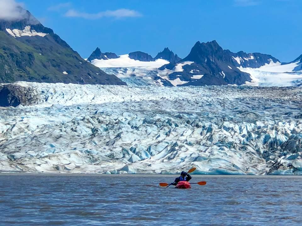 A double person kayak floats close to a glacier.