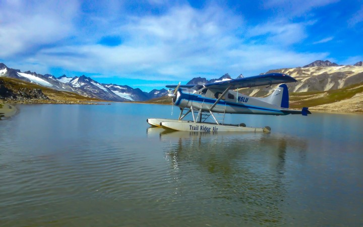 A silver and blue float plane sits on the water with mountains in the background.
