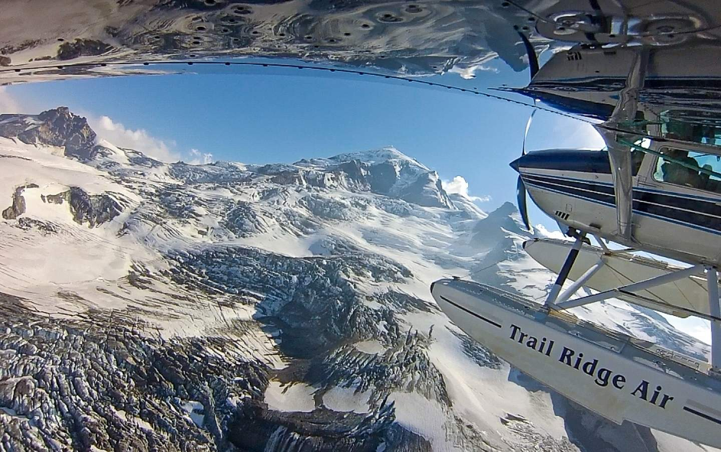 A view from under the wing of a bush plane as it flies above snow covered mountains.