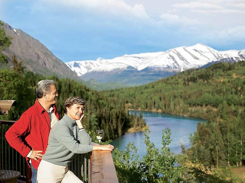 A couple stands at a viewing deck and looks out on the Kenai River Valley with mountains in the background.