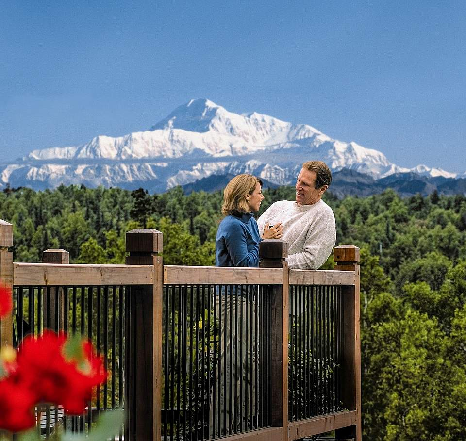 A couple stands on a balcony with Mt. Denali in the background.
