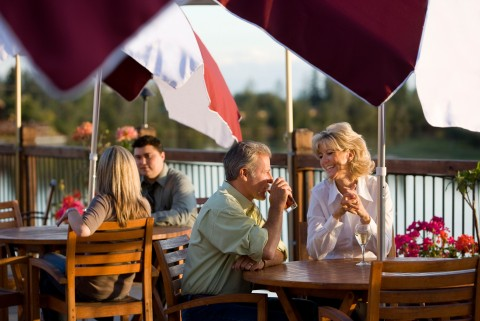 A smiling couple sits at a restaurant table outside overlooking the Chena River.