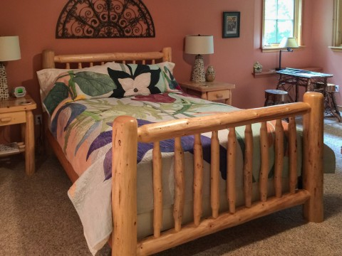 Inside a guest room showing a comfortable bed with a wooden bed frame.