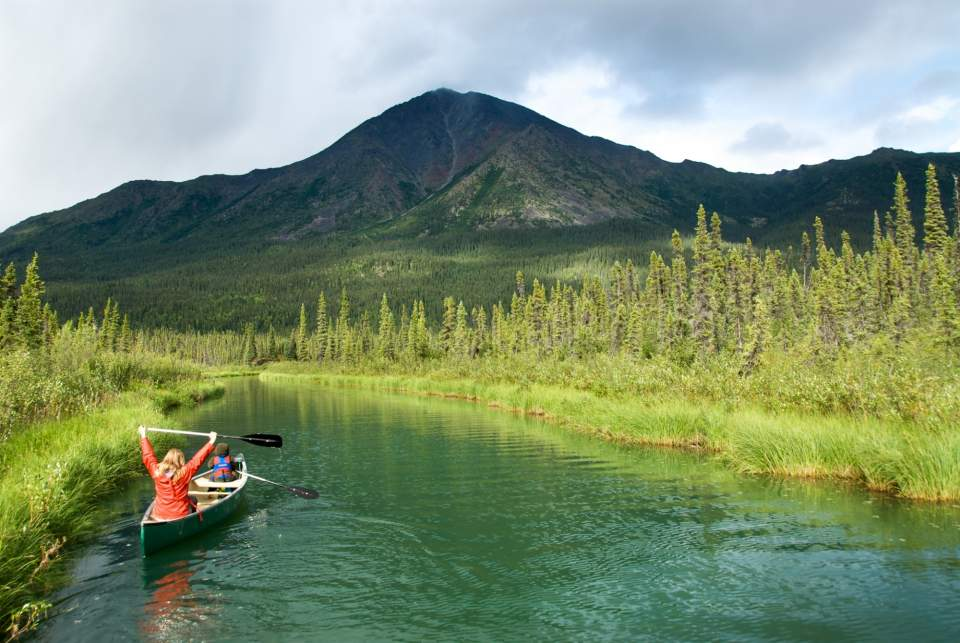 Two people float down a river in a canoe surrounded by lush Alaska landscape.