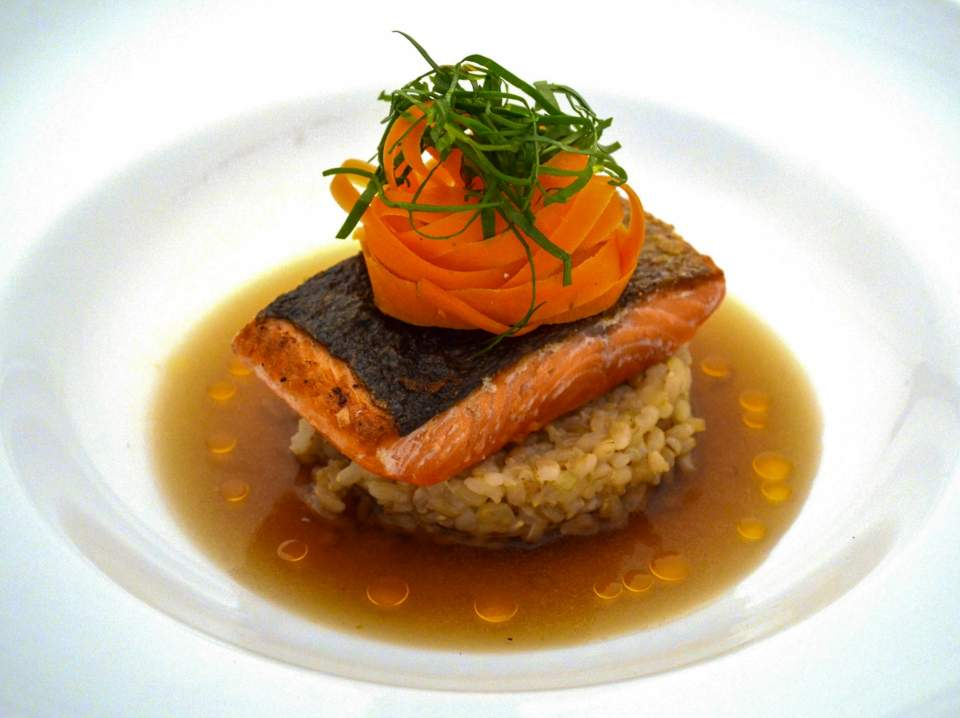 An beautiful dish of salmon resting on rice topped with swirled carrots and garnish.