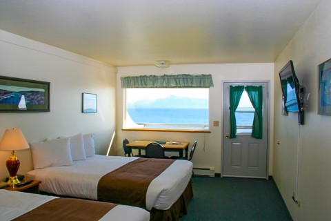 Inside of a guest room at the Ocean Shores Hotel with views from the window looking out onto the ocean.