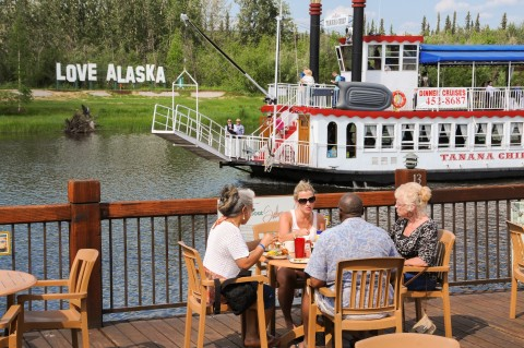 People dining outside on a deck overlooking a river while a river boat sails by.