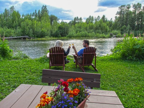 Two people in patio lounge chairs enjoy some wine together by the water.