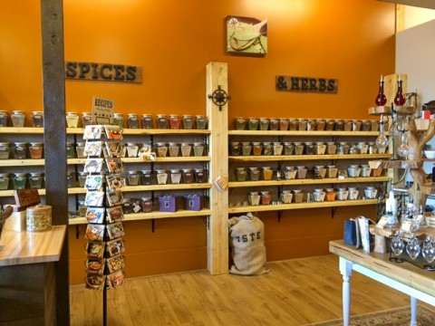 A shelf lined wall filled with jars of spices and herbs.